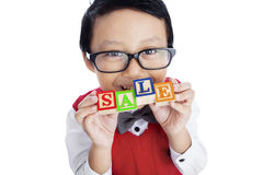 Asian boy hold SALE wooden alphabet toy - isolated. Asian boy is holding SALE wooden alphabet toy, isolated on white stock photo