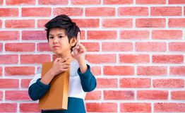 Asian boy holding book on brick wall background royalty free stock photography