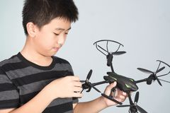 Asian boy holding and checking his hexacopter drone or quadrocopter toy in hand. Asian boy holding and checking his hexacopter drone or quadrocopter toy in hand stock image