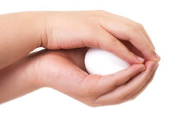 Asian boy holding an egg carefully with both hands Stock Photo