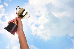 Asian boy holding a gold trophy cup for first place champion award on white background. royalty free stock images