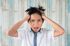 Asian boy holding his head feeling stress royalty free stock image