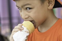 Asian boy holding the ice cream eating stock photography