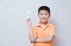 Asian boy holding a lamp, energy saving lamp,. On grey wall background with soft shadow Royalty Free Stock Photo
