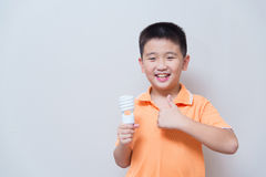 Asian boy holding a lamp, energy saving lamp,. On grey wall background with soft shadow Royalty Free Stock Images