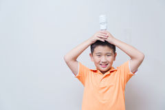 Asian boy holding a lamp, energy saving lamp,. On grey wall background with soft shadow Royalty Free Stock Photography