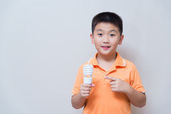 Asian boy holding a lamp, energy saving lamp,. On grey wall background with soft shadow Stock Image