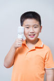 Asian boy holding a lamp, energy saving lamp,. On grey wall background with soft shadow Stock Images