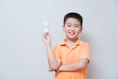 Asian boy holding a lamp, energy saving lamp, Royalty Free Stock Photos