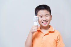 Asian boy holding a lamp, energy saving lamp,. On grey wall background with soft shadow Royalty Free Stock Photos