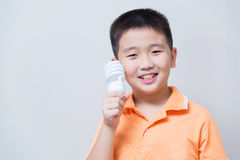 Asian boy holding a lamp, energy saving lamp,. On grey wall background with soft shadow Stock Photo
