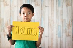 Asian boy holding paper note written `nothing` word royalty free stock photography