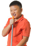Asian boy holds a broomstick as a microphone for singing Royalty Free Stock Photos