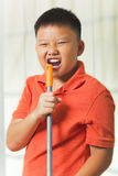 Asian boy holds a broomstick as a microphone Royalty Free Stock Photo