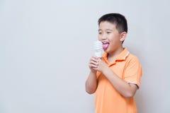 Asian boy joking gesture licking fake ice cream made with energy Royalty Free Stock Image