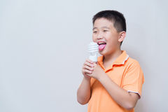 Asian boy joking gesture licking fake ice cream made with energy Royalty Free Stock Images