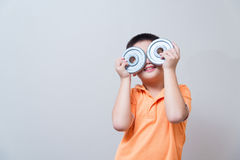 Asian boy joking gesture wearing fake glasses made with iron dum Stock Image