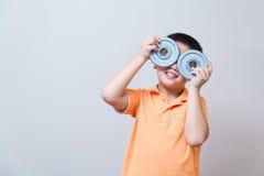Asian boy joking gesture wearing fake glasses made with iron dum Royalty Free Stock Photos