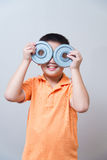 Asian boy joking gesture wearing fake glasses made with iron dum Stock Photo