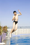 Asian boy jumpin into swimming pool. Teenager chinese body is jumping into the pool Royalty Free Stock Photos