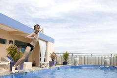 Asian boy jumpin into swimming pool Royalty Free Stock Photos