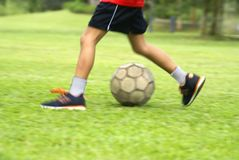Asian boy kicking soccer ball Royalty Free Stock Photo