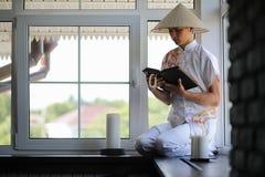Asian boy in kimono reading an old book Stock Photo