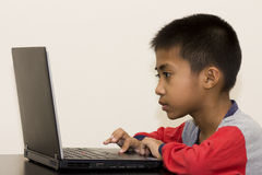 Asian Boy with Laptop. An Asian boy working with a laptop on a black table wearing pajamas Royalty Free Stock Photos