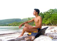 Asian boy with laptop on beach. Asian boy with laptop PC on tropical beach royalty free stock images