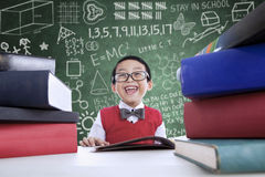 Asian boy laughing in class with stack of books. Close-up of Asian boy laughing in class with stack of books Stock Image