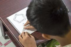 Asian boy learning and practicing to draw 3D shapes on drawing notebook on brown desk at home Stock Photos