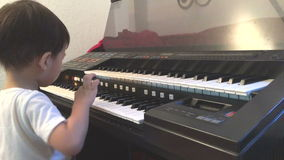 Asian boy learning to play electone stock video