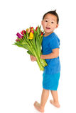 Asian boy with light handicap. And a colorful bouquet tulips Royalty Free Stock Image
