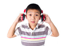 Asian boy listening music with headphones, isolated on white background Stock Image