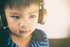 Asian boy is listening to music headphone. Royalty Free Stock Photo