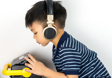 Asian boy is listening to music through headphone with cassette player. Stock Photo
