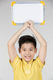 Asian boy is little smile with blank white board and looking cam Royalty Free Stock Images