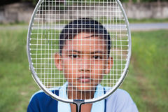 Asian boy. Looking through the badminton in the grass Royalty Free Stock Photos