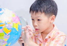 Asian boy looking at a globe. By magnifying glass Stock Photography