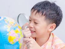 Asian boy looking at a globe. By magnifying glass Stock Photos