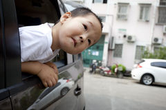 Asian boy looking out of the car Royalty Free Stock Images