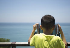 Asian boy looking the sea by Telescope Stock Images