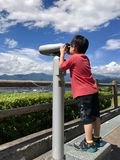 Asian boy looking through telescope with blue sky background stock photos