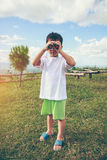 Asian boy looking through a telescope. Child relaxing holiday. V Stock Images