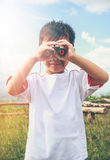 Asian boy looking through a telescope. Child relaxing holiday. V Royalty Free Stock Photos