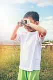 Asian boy looking through a telescope. Child relaxing holiday. V Royalty Free Stock Photography