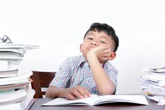 Asian boy looks bored studying on a desk and white background royalty free stock photo