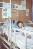 Asian boy lying on sickbed with infusion pump intravenous IV dri Stock Photography