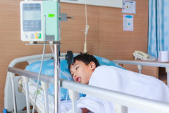 Asian boy lying on sickbed with infusion pump intravenous IV dri Stock Images