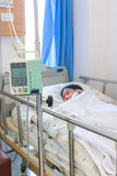 Asian boy lying on sickbed with infusion pump intravenous IV dri Stock Photo